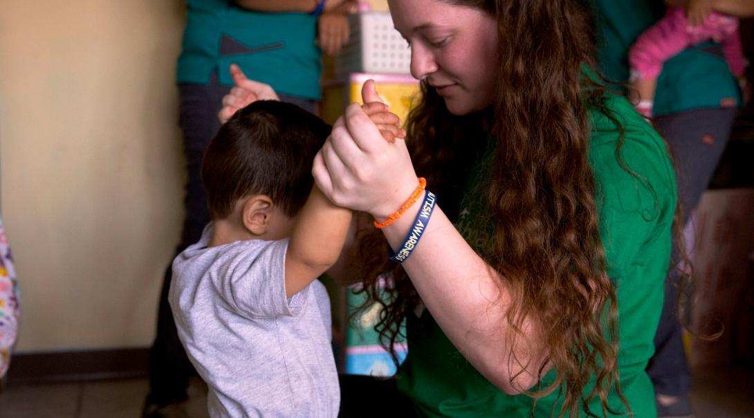 Pasante de trabajo social en el extranjero ayudando a un niño en un centro de cuidado.
